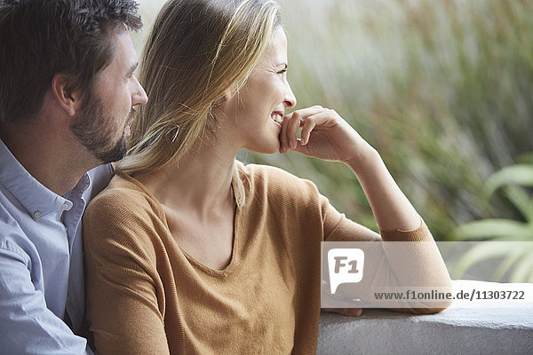 Smiling couple looking away on patio