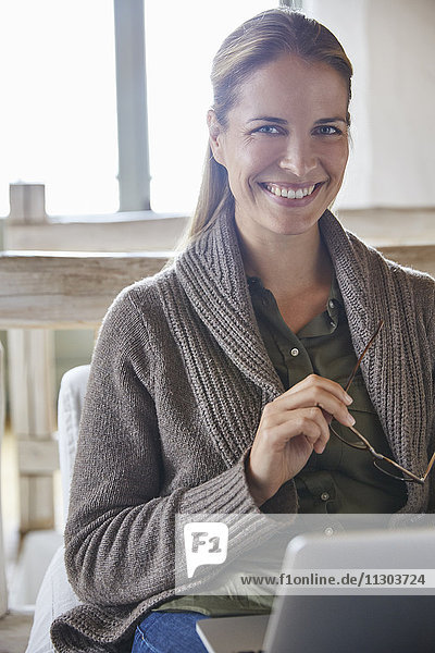 Portrait smiling woman using laptop