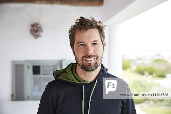 Portrait smiling brunette man wearing hoody on patio