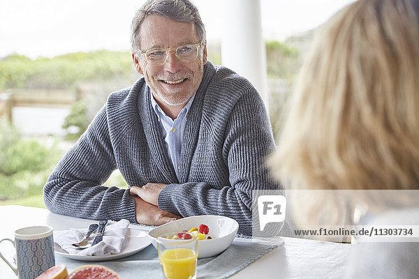 Senior couple eating breakfast on patio