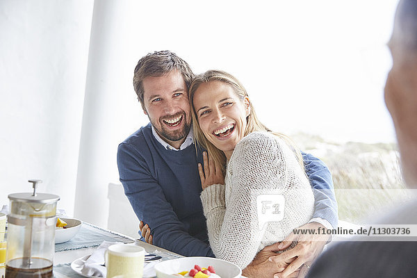 Happy affectionate couple laughing and hugging at patio breakfast