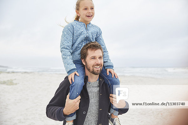 Father carrying daughter on shoulders on winter beach