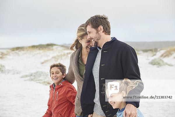 Happy family walking on winter beach