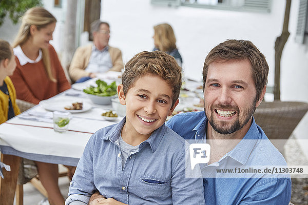 Portrait enthusiastic father and son enjoying patio lunch