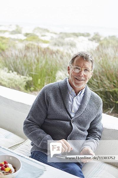 Portrait smiling senior man using digital tablet on beach patio