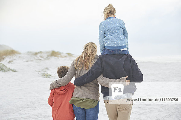 Affectionate family walking on winter beach