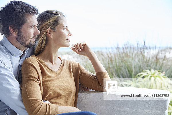 Serene couple looking away on patio
