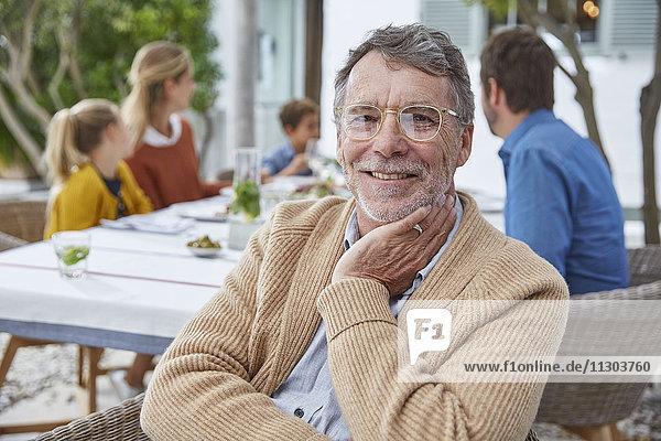 Portrait smiling senior man enjoying patio lunch with family