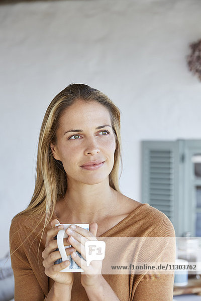 Serene woman drinking coffee and looking away on patio