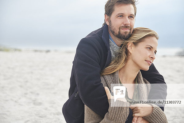 Serene affectionate couple hugging on winter beach