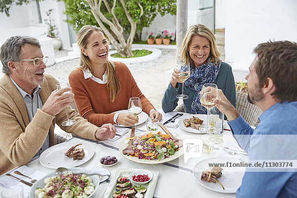 Couples laughing  drinking white wine and eating lunch at patio table