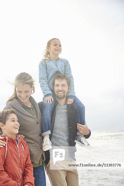 Smiling family walking on winter beach