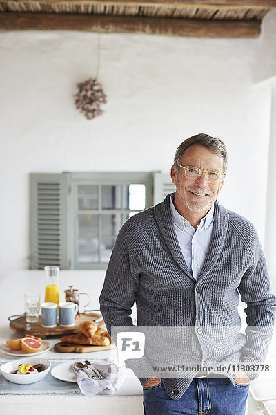 Portrait smiling senior man at patio breakfast table