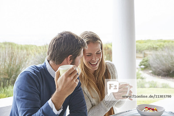 Laughing couple drinking coffee on patio
