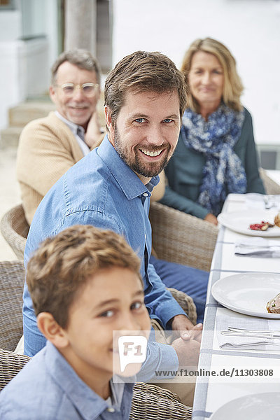 Portrait smiling multi-generation family enjoying patio lunch