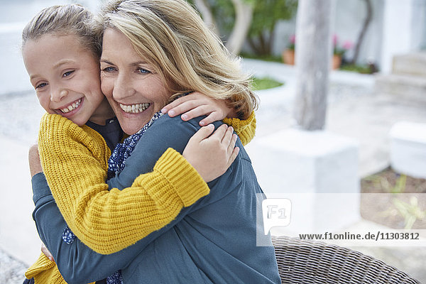 Enthusiastic grandmother and granddaughter hugging on patio