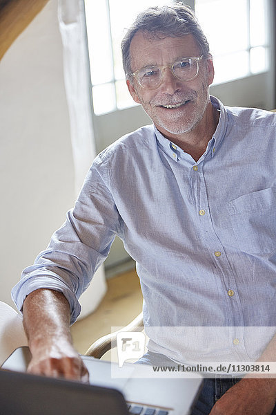 Portrait smiling senior man using laptop