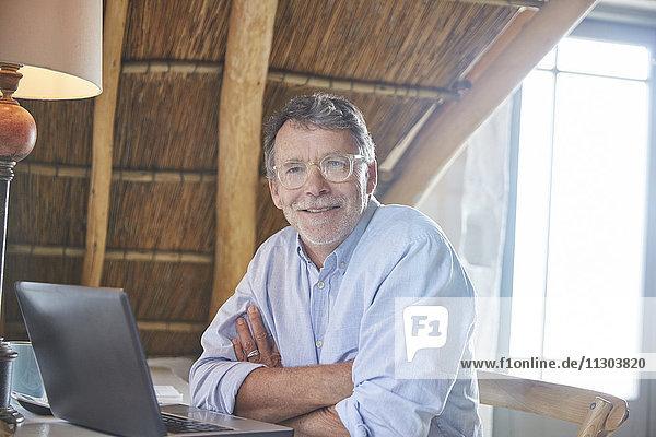 Portrait confident senior man using laptop