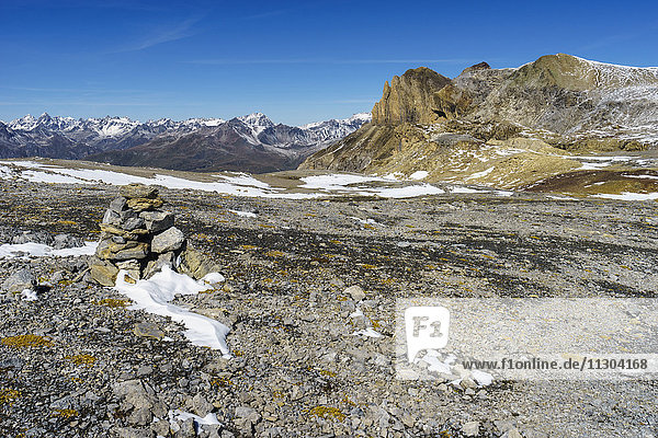 Cairn on the pass Fuorcla da Rims in the Lischana area  Lower Engadine  Switzerland. View to the Silvretta Alps.