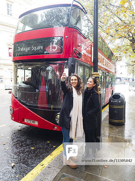 UK  London  two happy friends taking selfie with smartphone in front of red double-decker bus