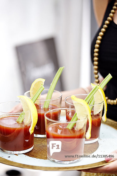 Glasses with bloody Mary on tray