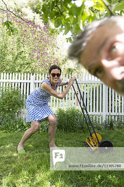 Smiling woman mowing lawn