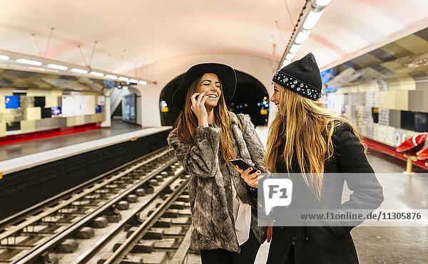 Paris  France  laughing tourists waiting at underground station platform