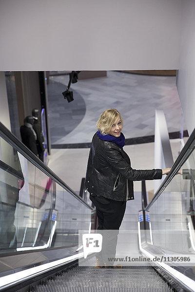 Woman on escalator in shop