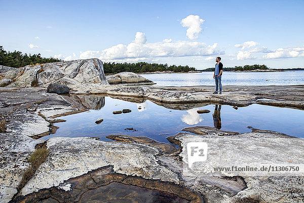 Mid adult man standing on rocks on sea coast