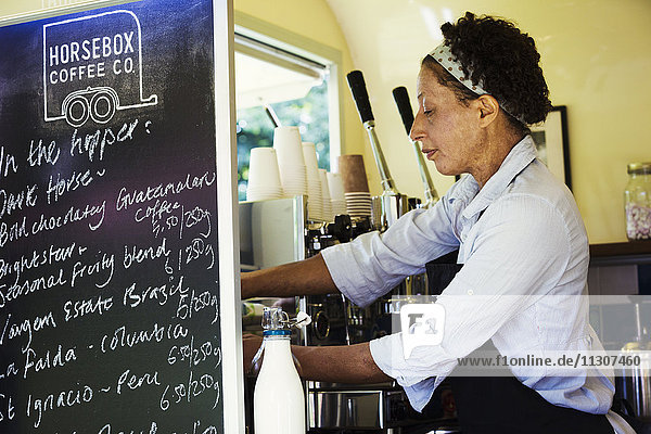 Woman standing in a mobile coffee shop.