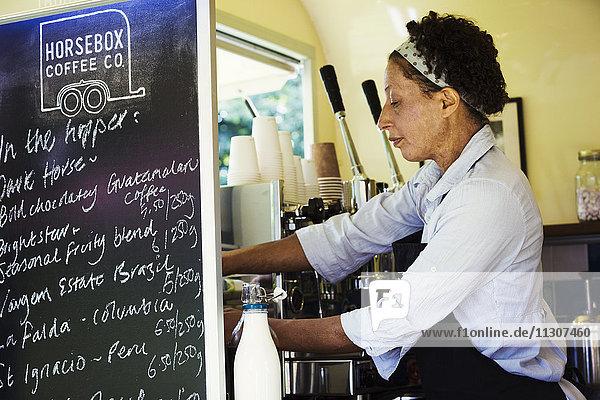 Frau  die in einem mobilen Café steht.
