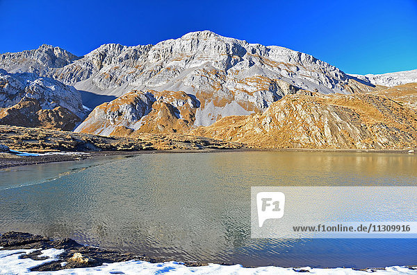 The Scniderhorn reflected in the lake at the Plan des Roses in the Bernese Alps  Switzerland. On a beautiful clear day with snow on the ground