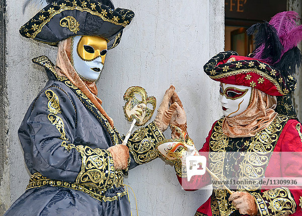 VENICE  ITALY - Two costumed ladies touching hands at the 2015 Venice Carnival:
