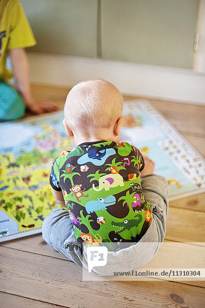 Baby boy looking at map