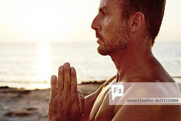 Man with clasped hands on beach
