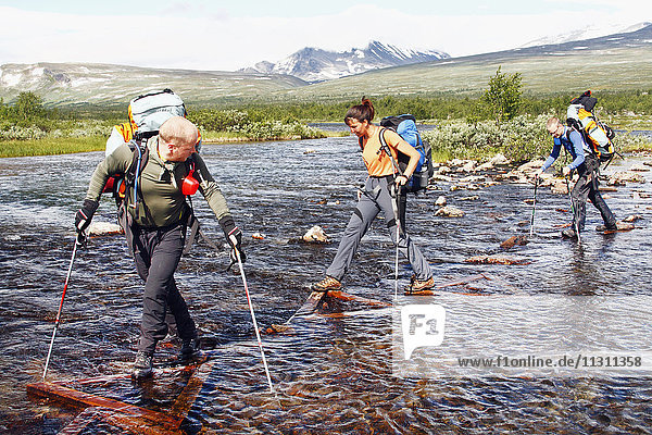 Hikers crossing river