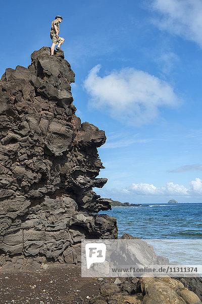 USA  Hawaii  Molokai  man on rock along the south coast MR
