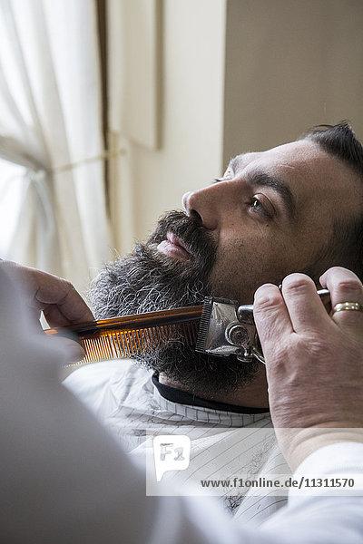 Friseur schneidet Männerbart