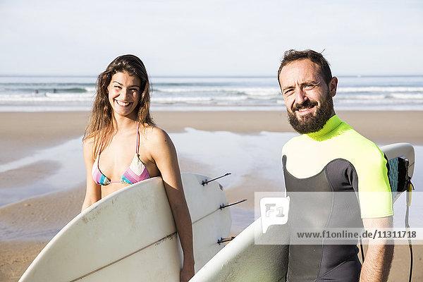 Glückliches Paar mit Surfbrettern am Strand