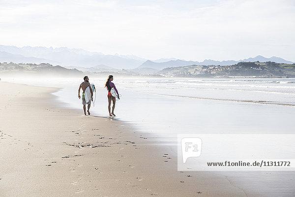Paar mit Surfbrettern  die am Strand spazieren gehen