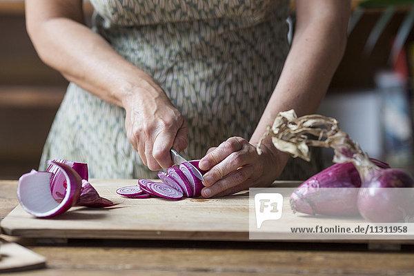Frau bereitet rote Zwiebeln für Zwiebelpesto zu