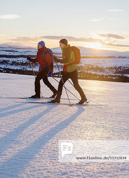 People skiing at sunset