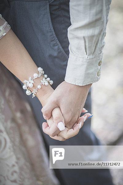 Nahaufnahme von Braut und Bräutigam beim Händchenhalten