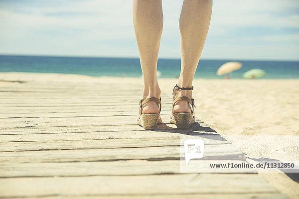 Beine einer Frau  die an der Strandpromenade steht.