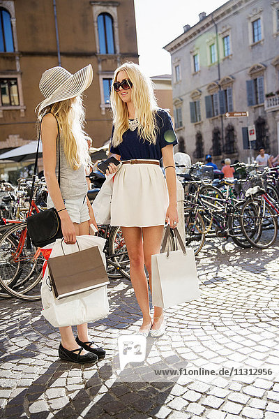 Mother and daughter with shopping bags standing in street