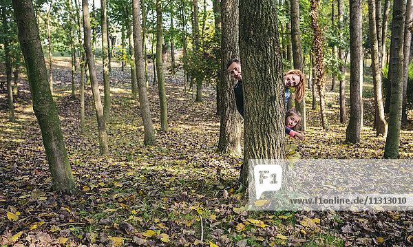 Eltern und kleine Tochter verstecken sich hinter einem Baumstamm