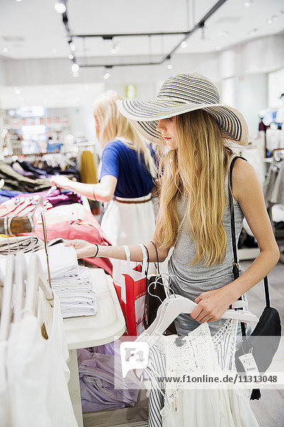 Young woman choosing clothes in store