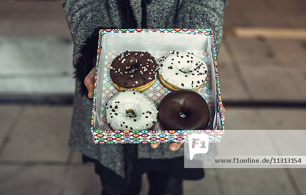 Woman holding box with doughnuts  partial view