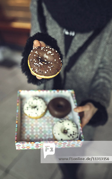 Woman holding doughnut with chocolate icing  partial view