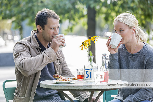 Mid adult couple drinking coffee in sidewalk cafe